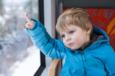 Cute little boy looking out train window outside, while it moving  travel