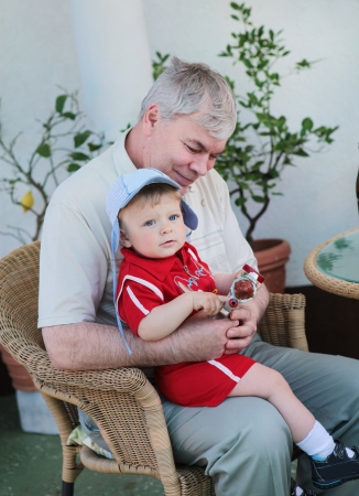 Grandfather with little baby boy sitting in summer garden Stock Photo - 17478225