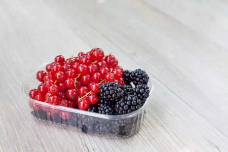 Bowl with different ripe berries - red currant and blackberry on wooden table in summer photo