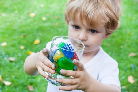 Beautiful toddler boy in summer garden with glass of colorful ice cubes Stock Photo - 17518895