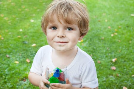 Beautiful toddler boy in summer garden with glass of colorful ice cubes Stock Photo - 17518886