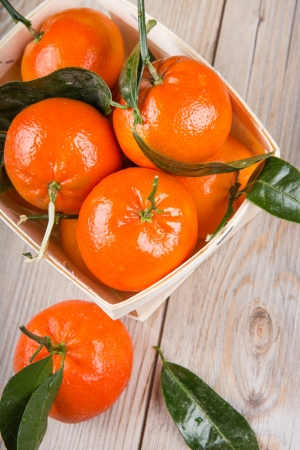 A wood rustic crate full of clementine mandarin oranges  Vertical format on wooden background Stock Photo - 17640557