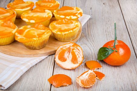 Fresh baked mini clementine cheesecakes in muffin forms with mandarines photo