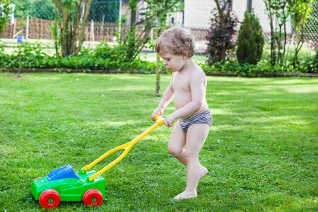 Little blond toddler boy playing with lawn mower machine in summer garden on sunny day Stock Photo - 17600771