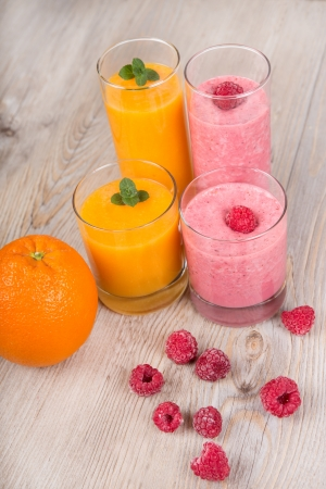 Fresh orange and raspberry smoothie drinks  On wooden background  Stock Photo - 17732099