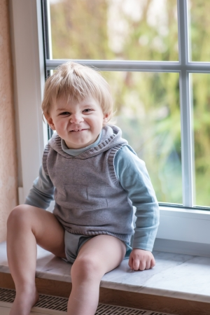 one year: Adorable blond toddler boy looking out of the window
