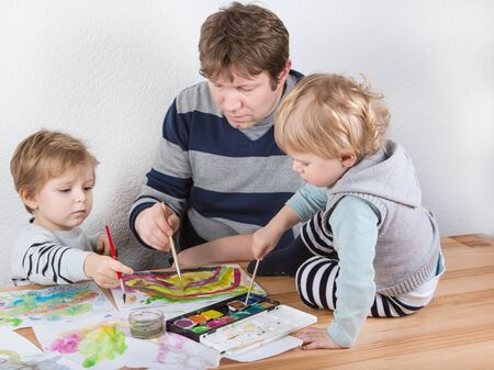 Father and two little boys siblings having fun painting at home photo