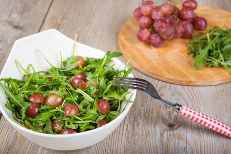Fresh rucola salad with red grapes on wooden table Stock Photo - 17818928
