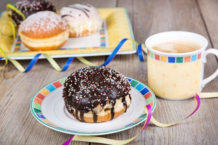 Chocolate and coconut donuts with carnival decoration  German traditional kreppel for carnival photo