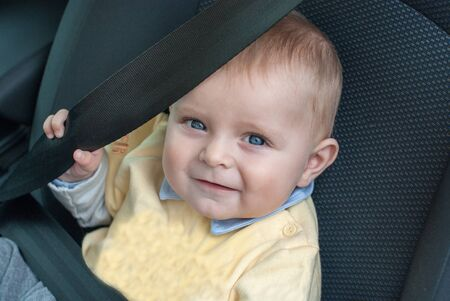 Adorable baby boy with blue eyes sitting in car, summer  photo