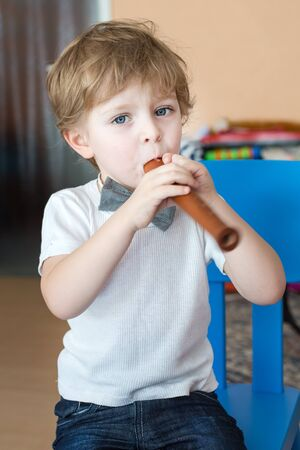 Little adorable boy playing wooden flute indoor photo