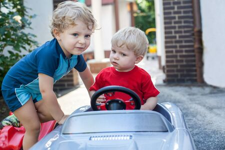 Two little brother toddlers playing with toy car in summer garden photo