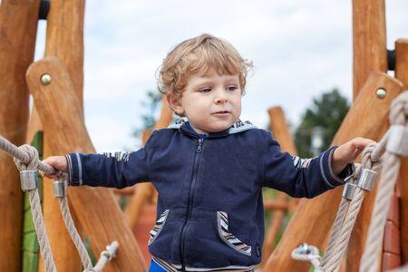 Little toddler boy having fun on playground in summer photo