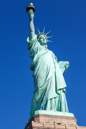 Die Statue of Liberty frei von Touristen und New York City Downtown an sonnigen frühen Morgen Lizenzfreie Bilder - 18422099