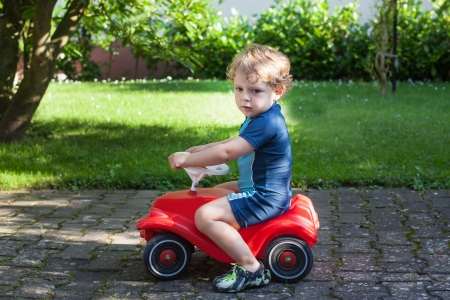 Little todder boy playing with big toy car in summer garden