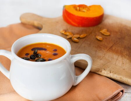 Pumpkin vegetable cream soup in white bowl with piece pumpkin on cutting board photo
