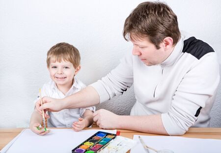 Father and little boy of two years having fun painting at home