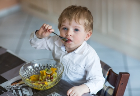 Little boy two years old eating fruit salad indoor photo