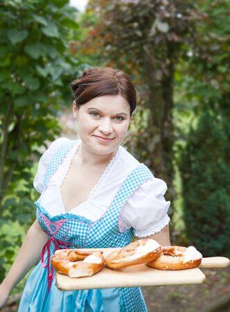 dirndl dress: Happy beautiful girl in dirndl dress holding Oktoberfest  pretzel in hands, Germany