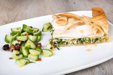 filo: Delicious spinach and feta cheese pie, with crispy filo pastry and Greek cucumber salad Stock Photo