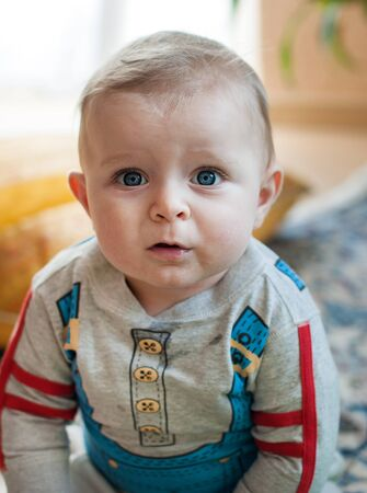 Little baby boy with big blue eyes and blond hairs at home photo