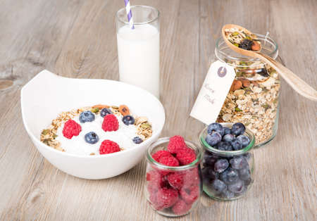 Healthy Breakfast with home made muesli, fresh raspberry and blueberry on textured background photo