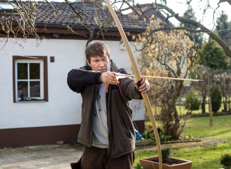 Young man archer training with the bow photo