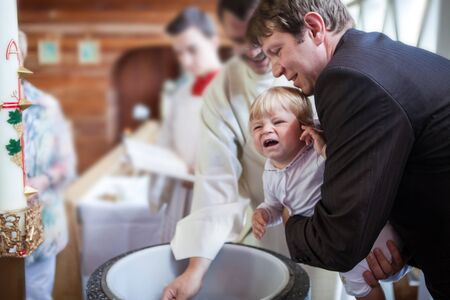 baptize: Little baby boy being baptized in catholic church holding by father