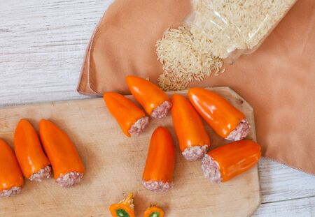 Stuffed orange pepper filled with ground meat, rice, onion on wooden cutting board photo