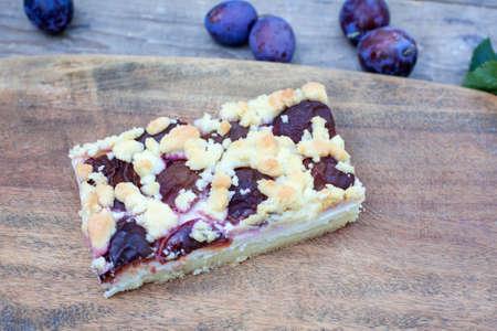 Fresh baked plum cake on wooden background photo