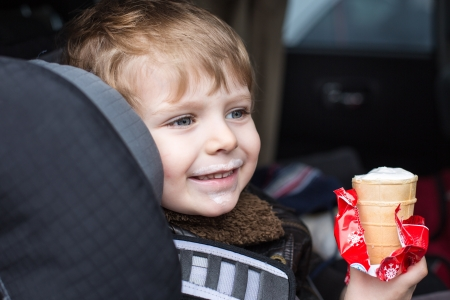 Adorable toddler boy with blue eyes in safety car seat eating sweet ice cream photo