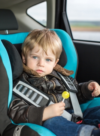 car seat: Toddler of one year with blue eyes in safety car seat eating candy Stock Photo