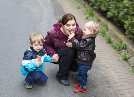 Young woman and two little boys having fun and eating ice cream, outdoors photo