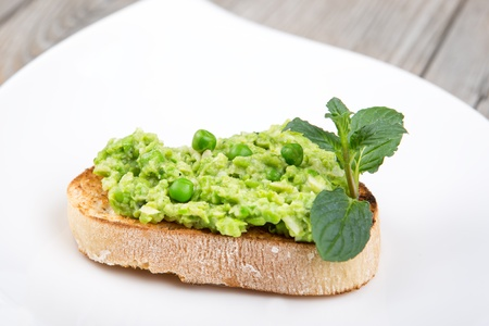 Delicious healthy canape with puree of raw beans and peas on white plate Stock Photo