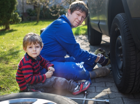 Little boy and his father changing wheel on car with pneumatic wrench Stock Photo - 19408394
