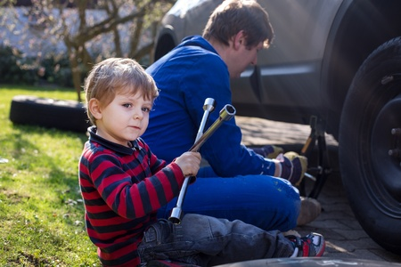 Little boy and his father changing wheel on car with pneumatic wrench photo