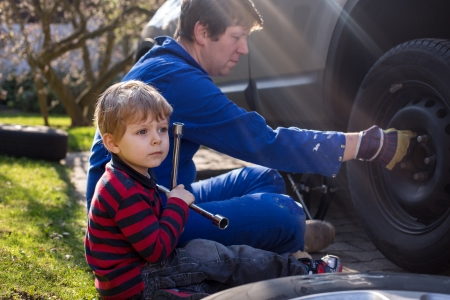 Boy of three years and his father changing wheel on car with pneumatic wrench photo