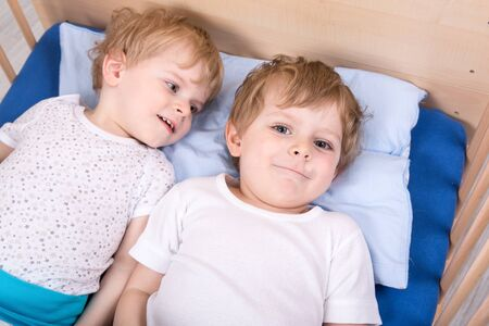 Two little toddler boys having fun in bed before sleeping