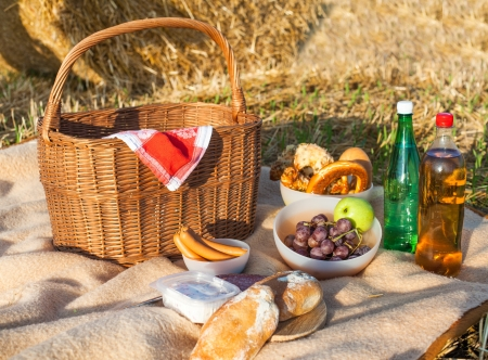 Picnic basket and different food and drinks on hay field