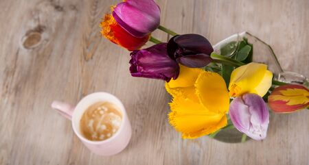 Colorful tulips and a cup of fresh coffee on wooden background photo
