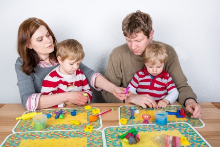 modeling clay: Happy family of a four having fun with modeling clay at home