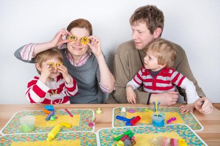 Famille heureuse de s'amuser à quatre avec la pâte à modeler à la maison