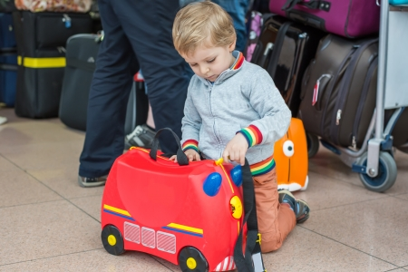Lovely three years old toddler boy with red suitcase at airport photo