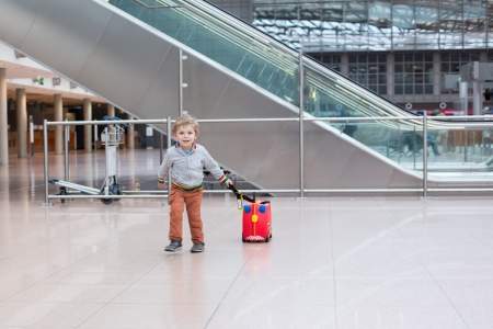 Lovely three years old toddler boy with red suitcase at airport Stock Photo