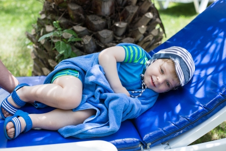 swimm: Little blonde toddler boy in swimm suit on couch, outdoors Stock Photo