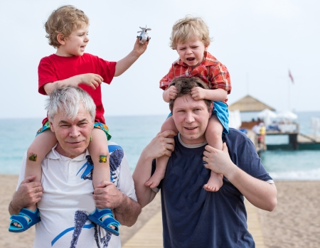 Grandfather and father giving two boys ride on shoulders on the beach in summer Stock Photo
