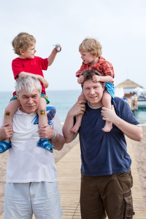 Grandfather and father giving two boys ride on shoulders on the beach in summer photo