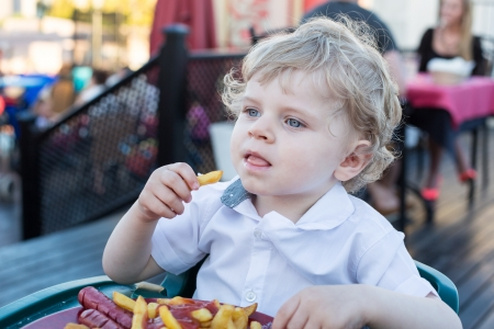 Blond little boy eating french fries in summer, outdoors Stock Photo - 20379143