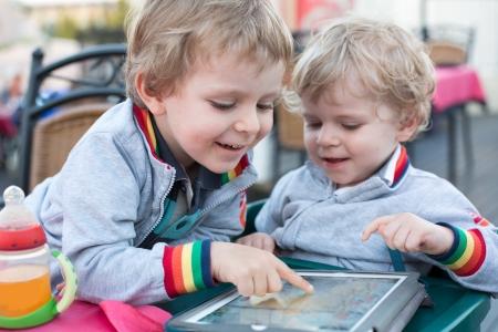 Dva malí kluci hrají s Tablet PC, venku Reklamní fotografie