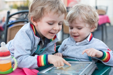 Two little boys playing with tablet pc, outdoors Stock Photo